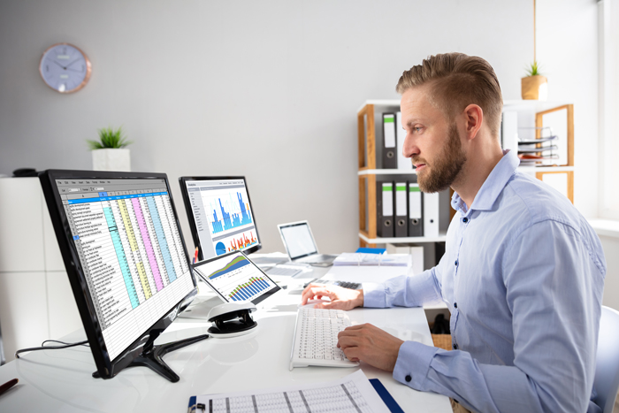 Businessperson Calculating E-Invoice Online On Computer At Office